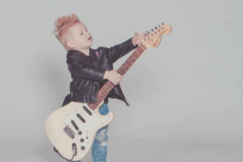 boy wearing black jacket holding electric guitar